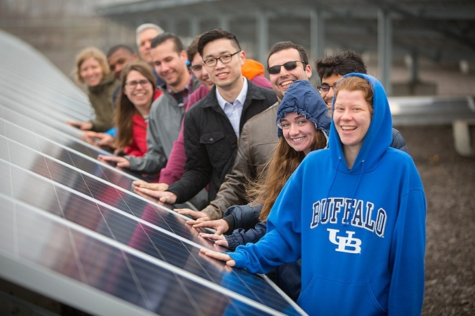 Students, one wearing a UB sweatshirt, stand with hands on a solar panel.