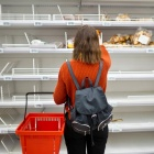 A shopper looking at empty grocery shelves.