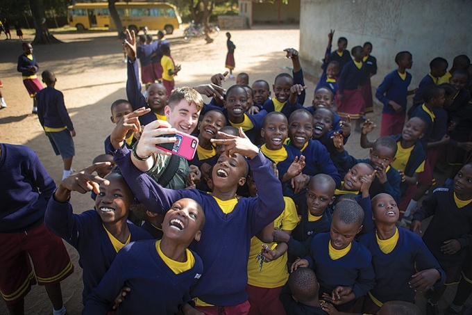Student Dylan McCaffrey takes a selfie with local schoolchildren.