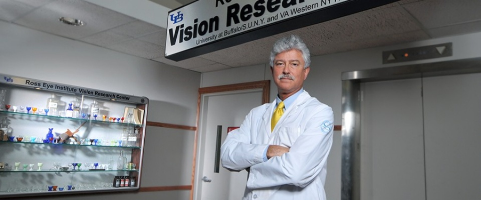 Steven Fliesler stands with arms folded beneath a sign for the Ross Eye Institute's Vision Research Center.