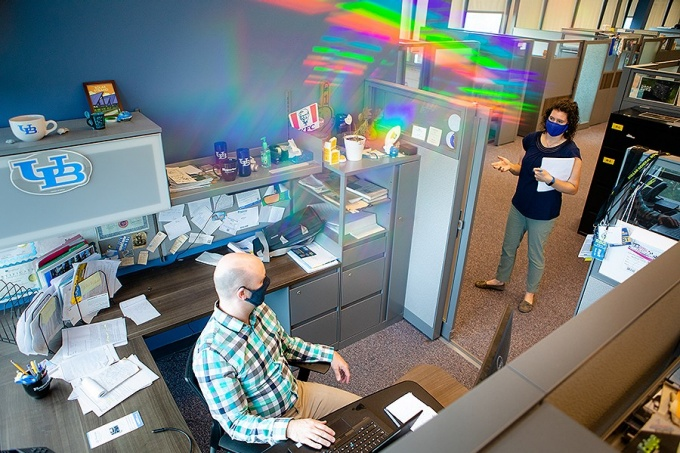 Two members of the UB staff demonstrate current physical distancing and face covering best practices while walking around and working in an office space in Crofts Hall in July 2020.
