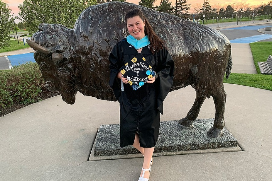 "Graduate Stephanie Sortino pictured in front of the bronze Buffalo near the Center for the arts on UB's North Campus. Her graduation cap reads, ""Quarantine Graduate I mastered it!""."