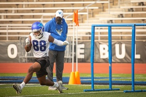 UB football team member works out as Coach Leipold watches.