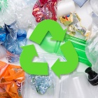 Various plastics with a recycling symbol in the foreground.