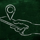 Concept of geotagging, a hand holding a smartphone with a location pin above it.