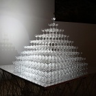 """Tide"" by Matt Kenyon features champagne classes stacked in a pyramid, each with a tiny house inside."