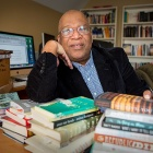 Cecil Foster sitting at a table full of books.