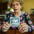 102 year old Marion Ahles holds a photo of herself riding a horse when she was young.
