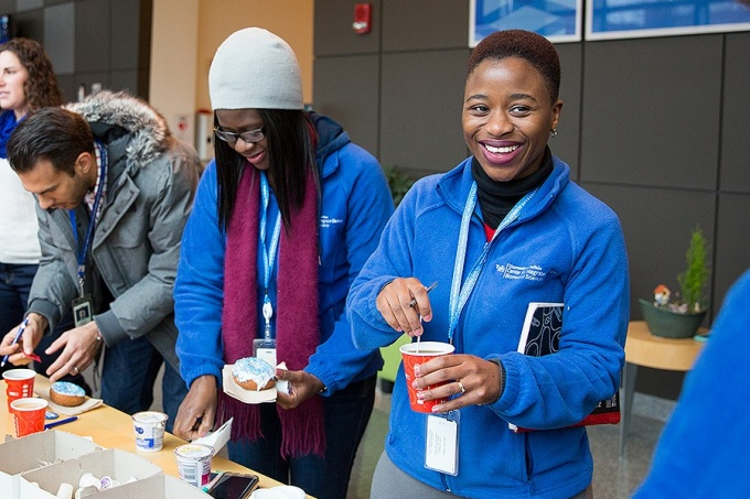 "UB employees enjoy some coffee and blue-themed doughnuts during a recent ""Get Blue"" promotional event on the Downtown Campus."