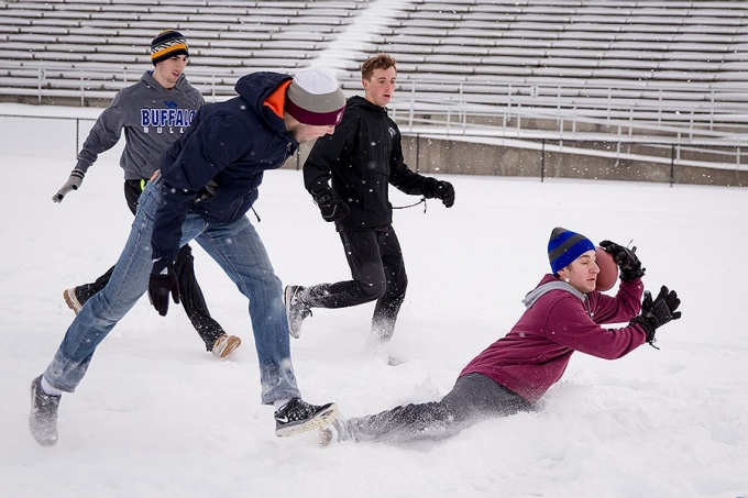 A group of sophomore friends play football in the snow on Kunz Field during winter break.