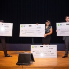 Winners of the 3-minute Thesis competition, (from left) Abdulrahman Hassaballah (third place), Riddhi Falk-Mahapatra (first place and People's Choice) and Konstantinos Plakas (second place) pose together on stage holding novelty checks.