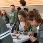 Undergraduate students from the School of Engineering and Applied Sciences write postcards to prospective new students.