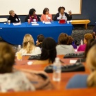 Four women seated at a table at the front of a lecture hall speak with participants at a PSS Diversity conferece.