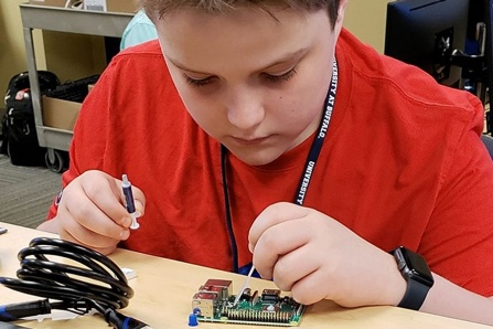 A student works on a circuit board during the cyber-security summer camp.