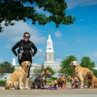 Sarah DeMerle poses with her pack, from left, Donnie, Teddy, Harold, Ricky, Seamus, Chanel, Maddie, Nala and Ash with Hayes Hall in the background.