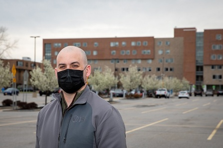 Adam Zangerle, wearing a face mask, standing in the lot in front of Greiner Hall.