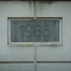 "A detail of a wall that features an inset plaque that reads, ""1986.""."