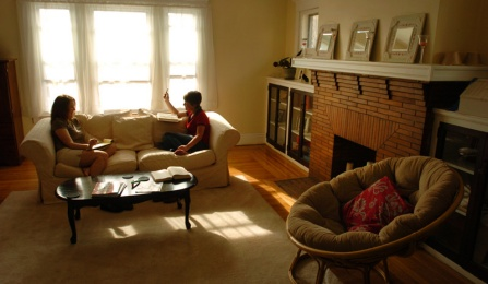 Two female students sit on the couch studying in the living room of a typical Buffalo apartment. A fireplace appears on the right of the room.