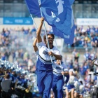 Fans cheering with pride as a UB flag bearer runs past the marching band.