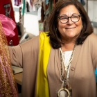 Fern Mallis smiling, surrounded by colorful costumes.