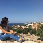 Lisa Khoury sitting on a rooftop looking out over a Syrian town and the ocean.