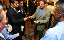 Business man at the center of a crowd handing business cards to UB students.