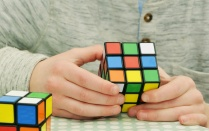 Hands holding colourful puzzle cube.