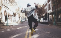 Young man jumping in the middle of a street.