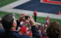 Parent photographing football game.