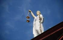 A statue of lady justice against a bright blue sky.