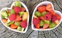 Two heart shaped bowls full of fresh fruit.