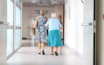 Middle age woman assisting elderly woman down a hospital hallway.