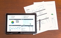 Tablet with analytics showing and paper with data underneath it.