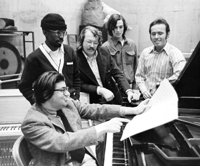 "Rehearsal of Morton Feldman's ""Pianos and Voices"" in Baird Hall, 1972. Morton Feldman at piano, with, from left, Julius Eastman, Jan Williams, William Appleby (student), David Del Tredici."