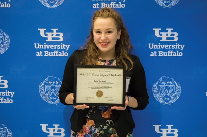 Photo of a UB student holding a scholarship plaque