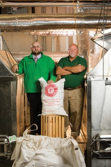 Adam and Bob Patterson proudly display a bag of their finished malt.