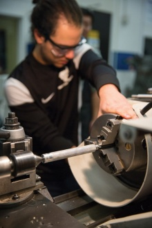 A student uses a lathe to fabricate a metal hammer in Engineering Machine Shop.