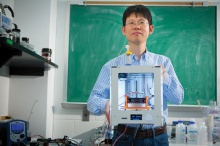 Chi Zhou with the 3-D printer he uses to make 3-D graphene.