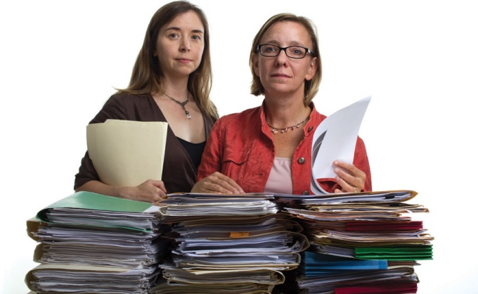Portrait of Annette Semanchin Jones and Patricia Logan-Greene standing in behind stacks of files