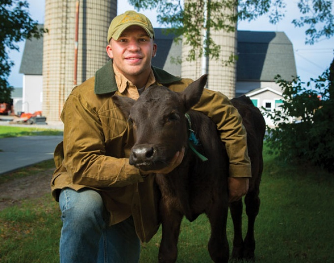 Portrait of UB wrestler Colt Cotten on a farm with a calf.