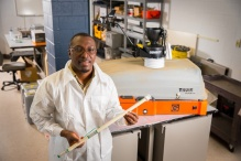 Erasmus Oware in his lab, showing the soil-zapping device he created.