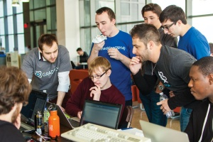 UB Hackathon sponsors and organizers gather around Nate Burgers for a closer look at the progress on his hack.