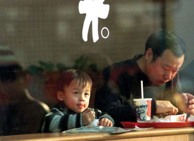 A young boy and his father at a KFC in Shanghai.