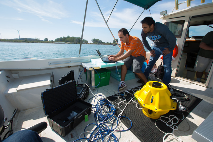 Hovannes Kulhandjian, left, and Zahed Hossain get ready to test an underwater wireless network in Lake Erie.