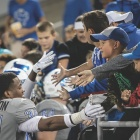 UB Football team interacting with kids in the fan crowd.