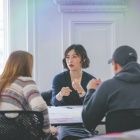 Graduate students gathered at a discussion table having conversation.