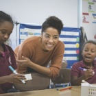 UB Graduate student working with children in a classroom.