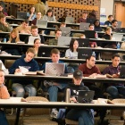 Students taking notes in a lecture hall.