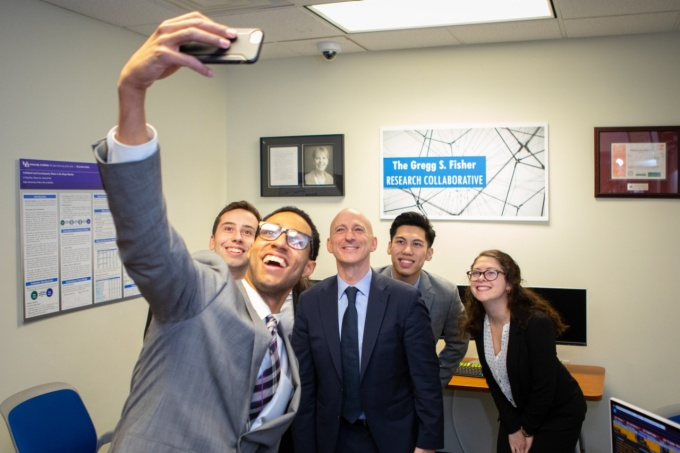 Joel Sims, a master's candidate in UB's finance program in the School of Management, takes a group selfie with fellow students and benefactor Gregg Fisher (third from left). .