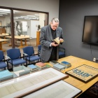 "Rev. Msgr. J. Patrick Keleher (""Father Pat""), director and campus minister for the Newman Center at UB, stands near the James Joyce Collection within the University at Buffalo Libraries."